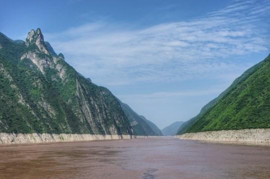 Das Einzugsgebiet des aufgestauten Yangzi-Flusses erstreckt sich ca. 400 Kilometer flussaufwärts und bildet damit ein gigantisches Reservoir für die ergiebigen Niederschläge während der zwei Regenzeiten von Mai bis August (Niveauunterschied sichtbar an den kargen Felswänden). Die Vorteile des Dammbaus (Wasserregulierung, Erzeugung von Strom aus erneuerbarer Ressource) bringen zahlreiche negative Folgen mit sich. Flussaufwärts: u.a. Umsiedlung Millionen von Menschen, Bodenerosion; flussabwärts: u.a. Fehlen von Nährstoffen, Artensterben