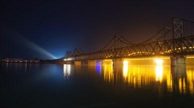 """Blick auf Nordkorea und die Brücke des Grenzübergangs bei Nacht. Ja, auch in Nordkorea brennt nachts Licht. Der Schein trügt jedoch: Mit Ausnahme des Zuges auf der Brücke und der Flutlichter sind die anderen """"Lichter"""" Reflexionen der casinoartig beleuchteten chinesischen Seite"""