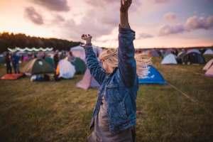 woman-in-jean-jacket-raises-arms-near-tents-in-festival-campsite