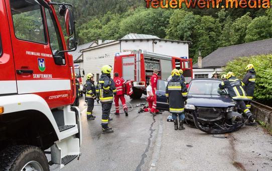 Feuerwehr und Rettungsdienst retten eine verunfallte Person aus einem Unfallfahrzeug