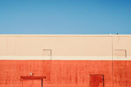 a brick red cream paint building against a blue sky