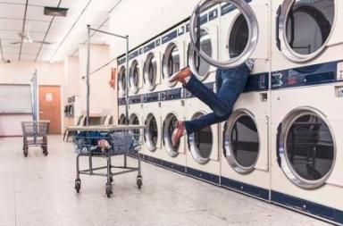 A man's legs sticking out of a washing machine in a launderette