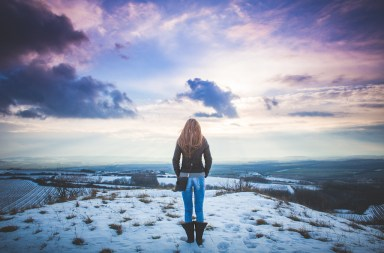 Girl at top of snowy mountain looking at sunset sky.