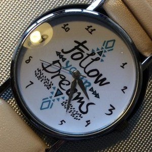 A white watch face inscribed Follow Your Dreams