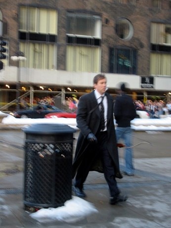 Une scène du futur film, Nicolas Cage marche, en vêtements d'hiver, un arc sur le dos.