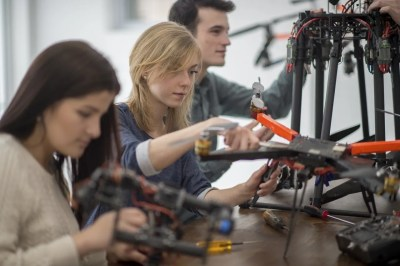 A group of college students are working on the mechanics for a robotics and drone project in university.