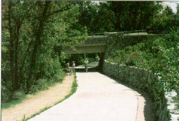 photo: Concrete, multiuse path with trees on the left, a wall and landscaping on the right