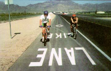 photo: Two bicyclists riding in a dedicated bike lane