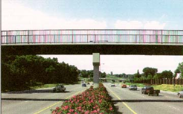 photo: six lane highway divided by a median with flowers, spanned by a bridge