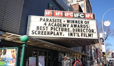 "A black and white marquee celebrating the win of the film ""Parasite."""