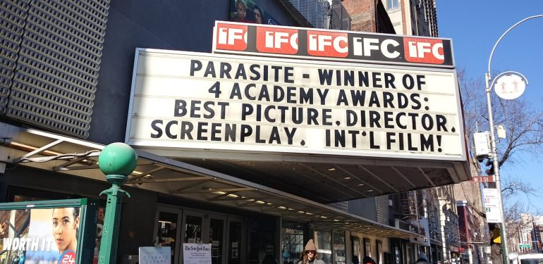 """A black and white marquee celebrating the win of the film """"Parasite."""""""