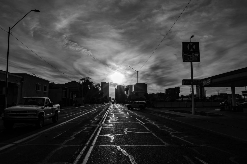 A black and white shot of an empty street in Phoenix, with a cloudy sky overhead.