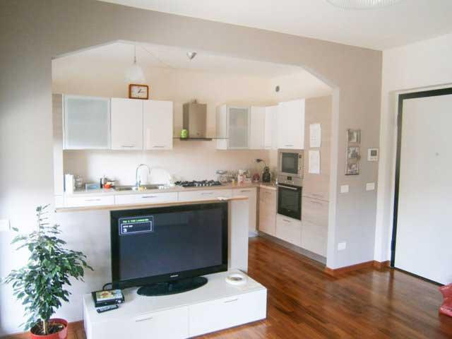Cucina e soggiorno ad arco con muretto divisorio
