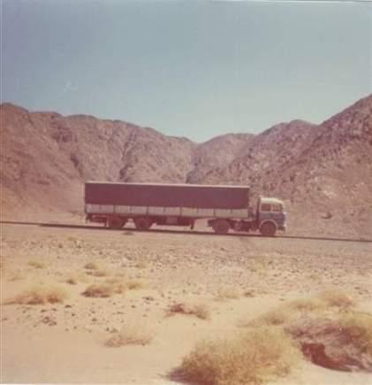 Camion des transports Lombard, sur fond de montagne. Le chauffeur doit être en train de courir après les chamelles. Les chêvres, c'est bien aussi.