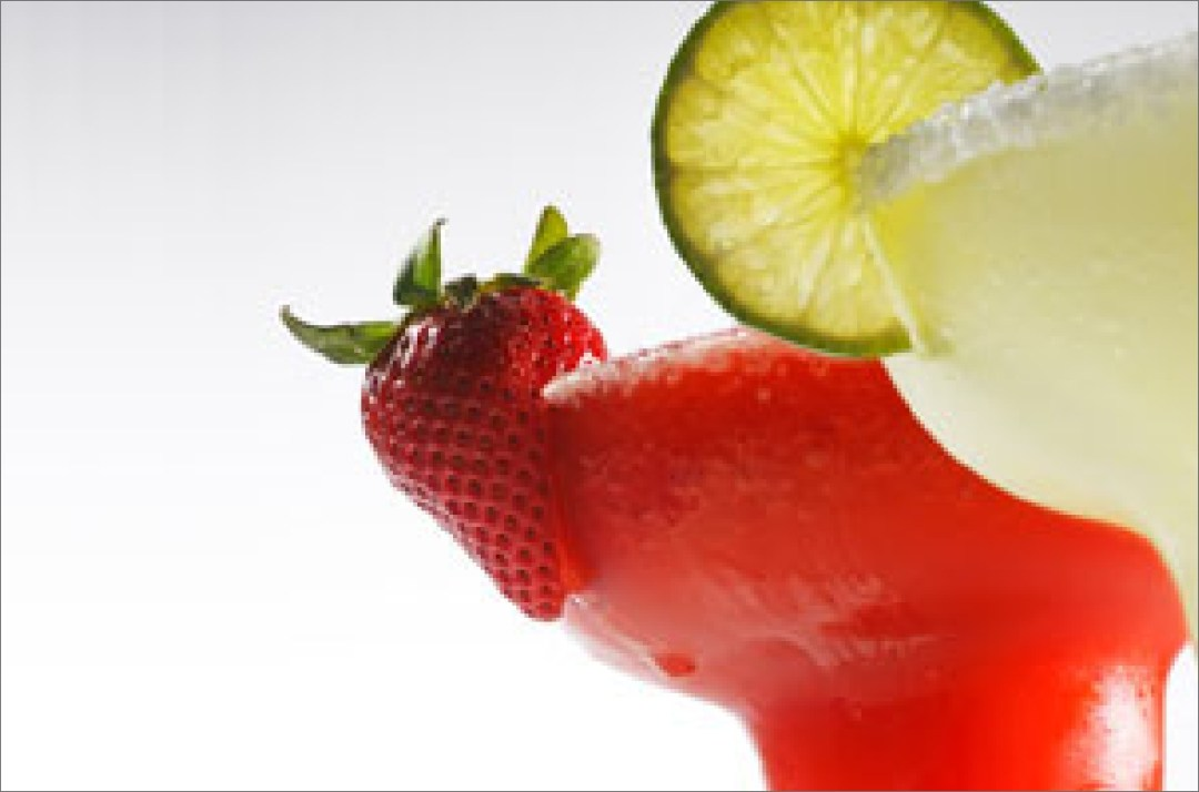 Close up of a strawberry and lime margaritas with garnishes