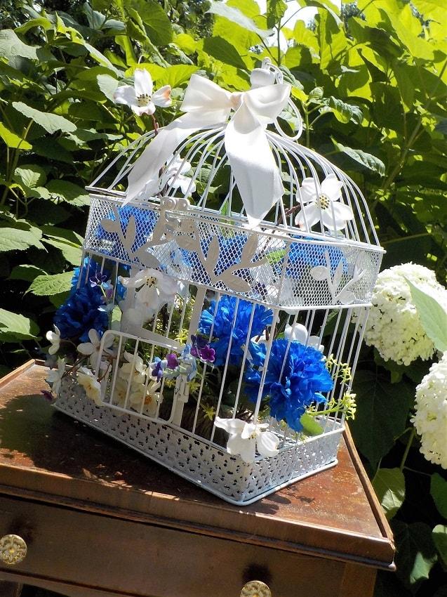 centro de mesa con jaula de canarios llena de flores