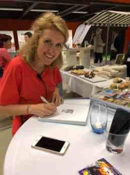 Dokter Tamara, Tamara de Weijer signeert maar al te graag die stapel boeken voor Cindy van Domburg van de Biefit Gezondheidswinkel — bij Jaarbeurs.