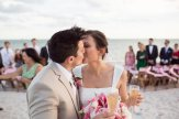 bride and groom kiss with guest in the background
