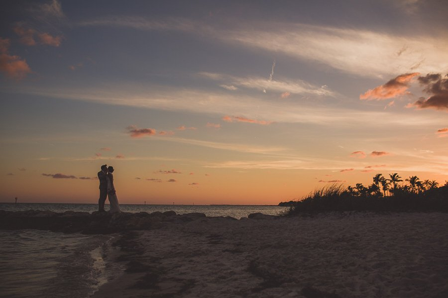 married couple kiss at sunset at smathers beach in key west florida