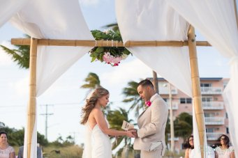 groom reads his wows during their beach ceremony