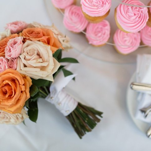 detail photo of wedding bouquet and wedding cake