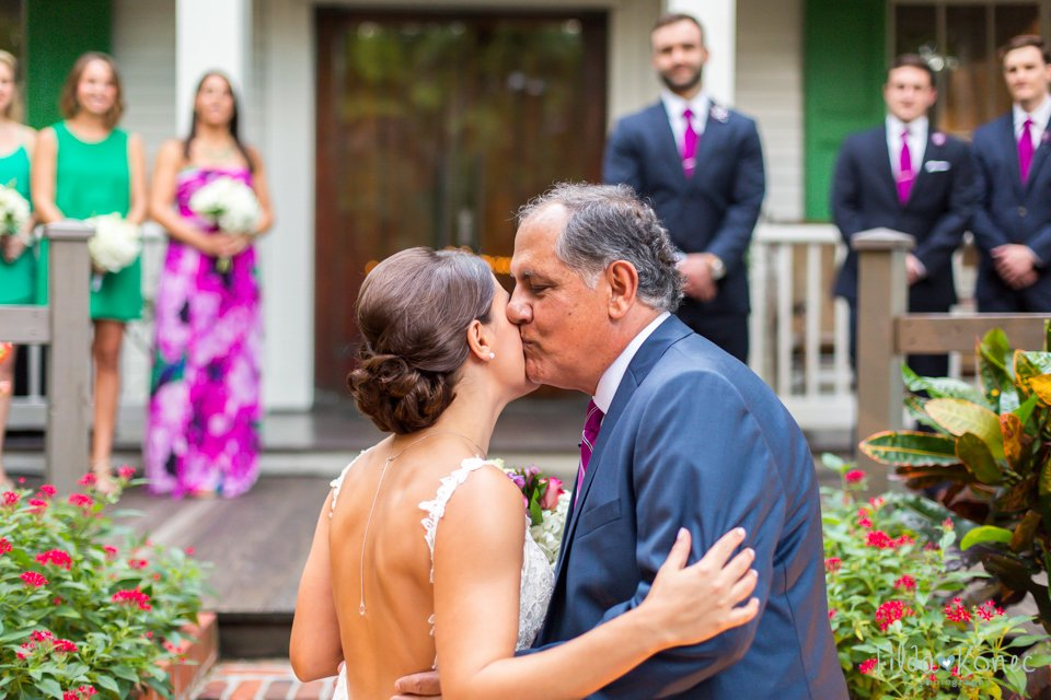 father kisses his daughter at her wedding