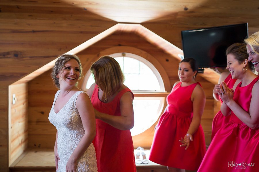 mom helping the bride in to her dress