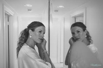 bride in the mirror putting ear rings on