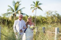 father walks his daughter to the beach altar for key west wedding