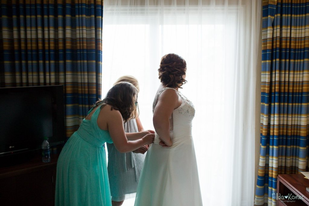 mom and sister help the bride button up her wedding dress