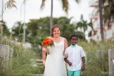bride and her son walk the isle for their beach wedding