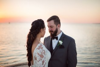 bride and groom on the beach during sunset