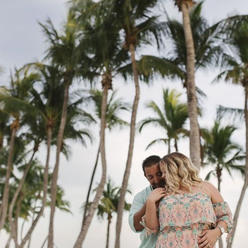 couple cuddling with palm trees on the beach