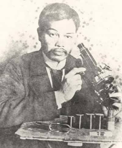 Antonio Luna poses with a microscope at the Institut Pasteur in Paris, France