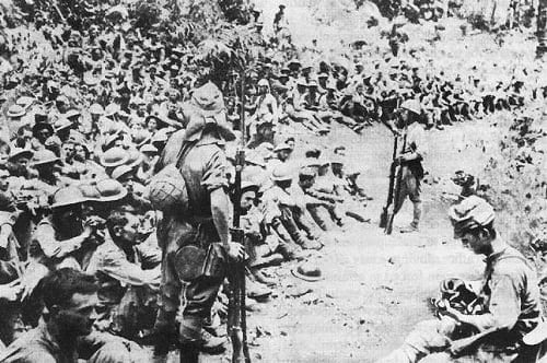 Japanese soldiers guard American and Filipino prisoners of war after the conclusion of the Battle of Bataan