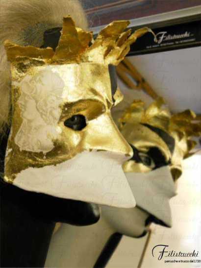 immagine di un manichino che indossa la maschera detta larva o bauta, tipica di venezia, maschera neutra, non espressiva, ma in questo caso dipinta d'oro