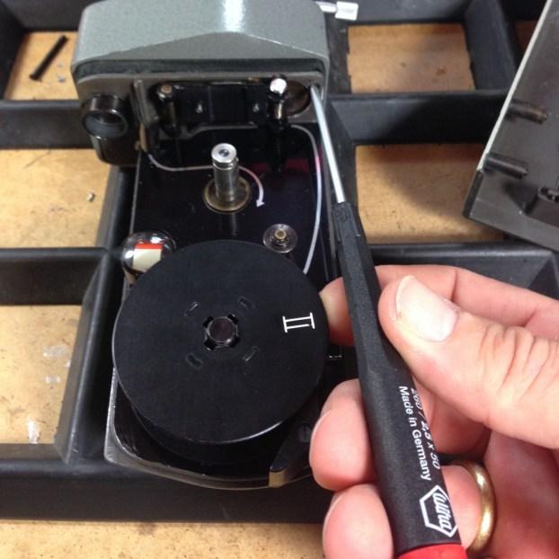 Nach entfernen des Filmkammerdeckels kann auch die andere Schraube gelöst werden, die den Kamerakopf mitträgt.