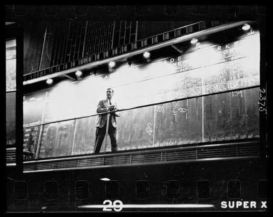 "Unidentified man standing in front of a ""Trade"" board on which he records a ""Market Score"" at the Chicago Board of Trade"