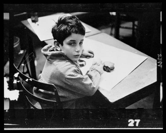 Young boy, half-length portrait, seated at desk, in classroom in Chicago, Illinois