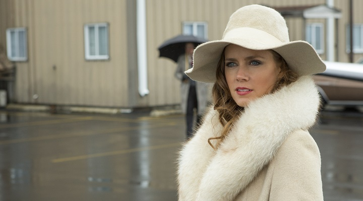Sydney Prosser (Amy Adams) stands on the Teeterboro Airport Tarmac in Columbia Pictures' AMERICAN HUSTLE.  (Amy Adams coat, hat: vintage)