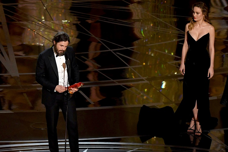"""US actor Casey Affleck (L) delivers a speech on stage next to actress Brie Larson (2ndR) after he won the Best Actor award in """"Manchester By The Sea"""" at the 89th Oscars on February 26, 2017 in Hollywood, California. / AFP / Mark RALSTON (Photo credit should read MARK RALSTON/AFP/Getty Images)"""