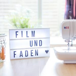 Film und Faden in einer Lichtbox neben Nähmaschine