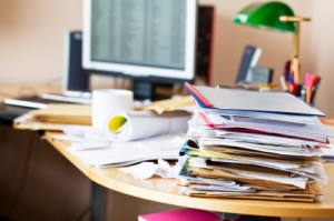 chaotic desk, covered with all kinds of paper, files and envelops