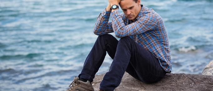 depressed man sitting by the water