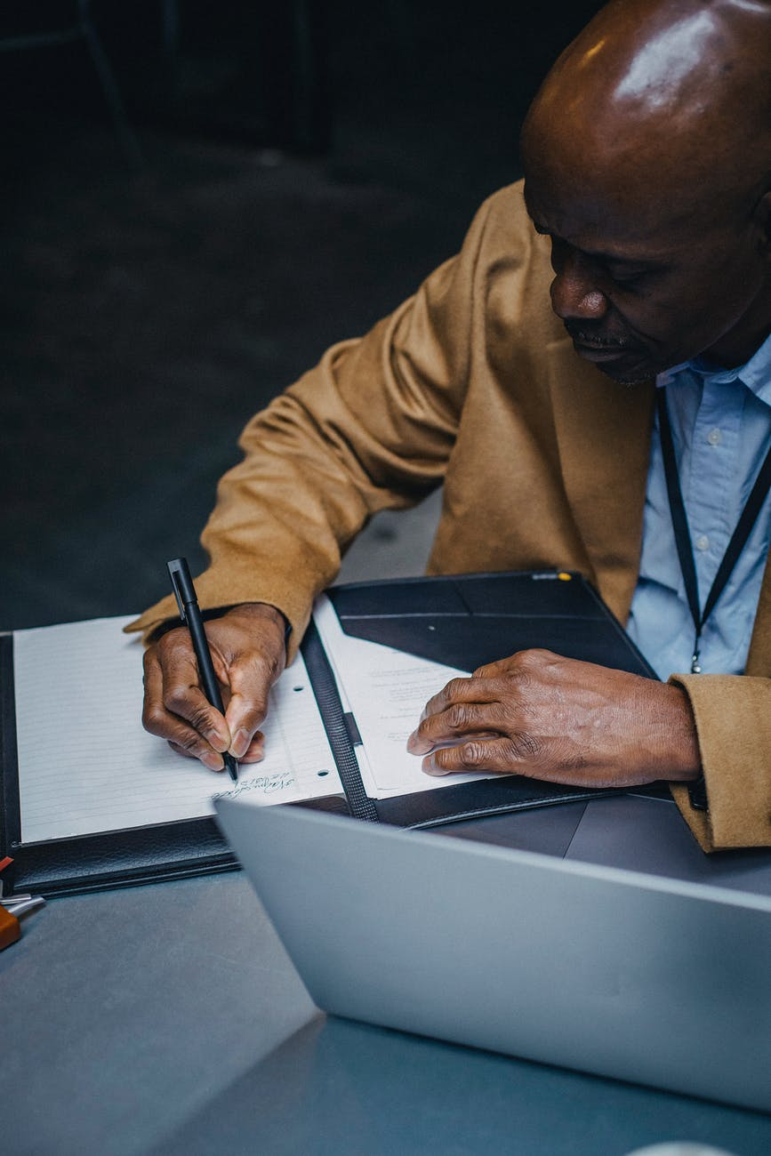 an image of a man writing on a booklet of foolscaps  with a pen