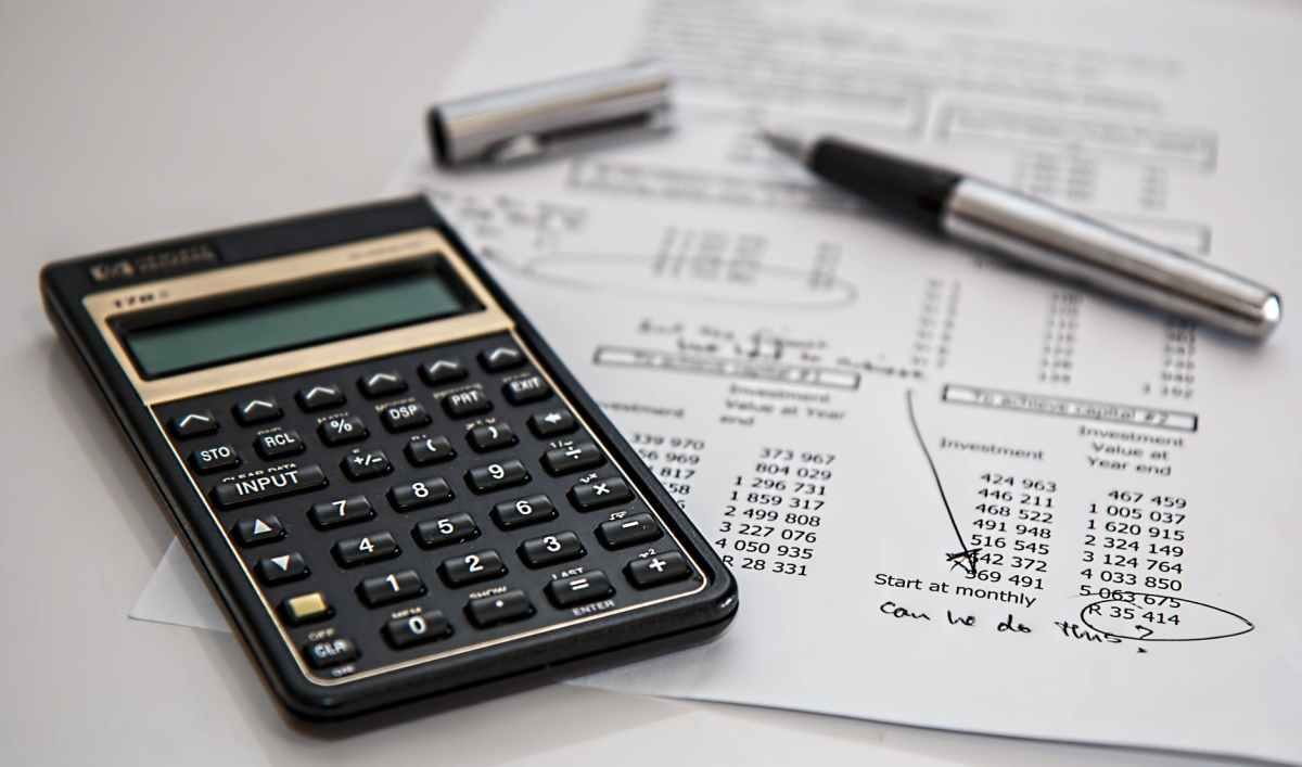 Imagine of a calculator,  pen and piece of printed paper of a budget on a white surface