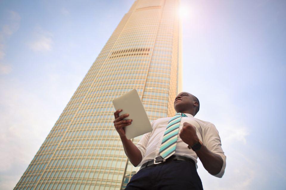 Mann steht vor Wolkenkratzer