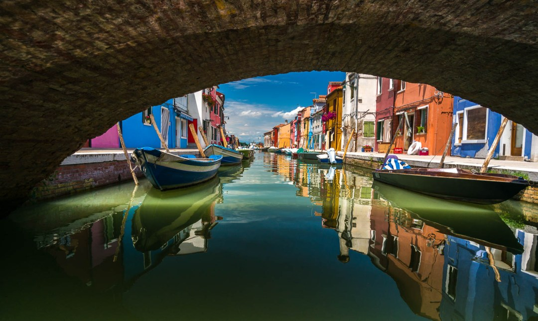 Colourful buildings in Burano under bridge with boats.