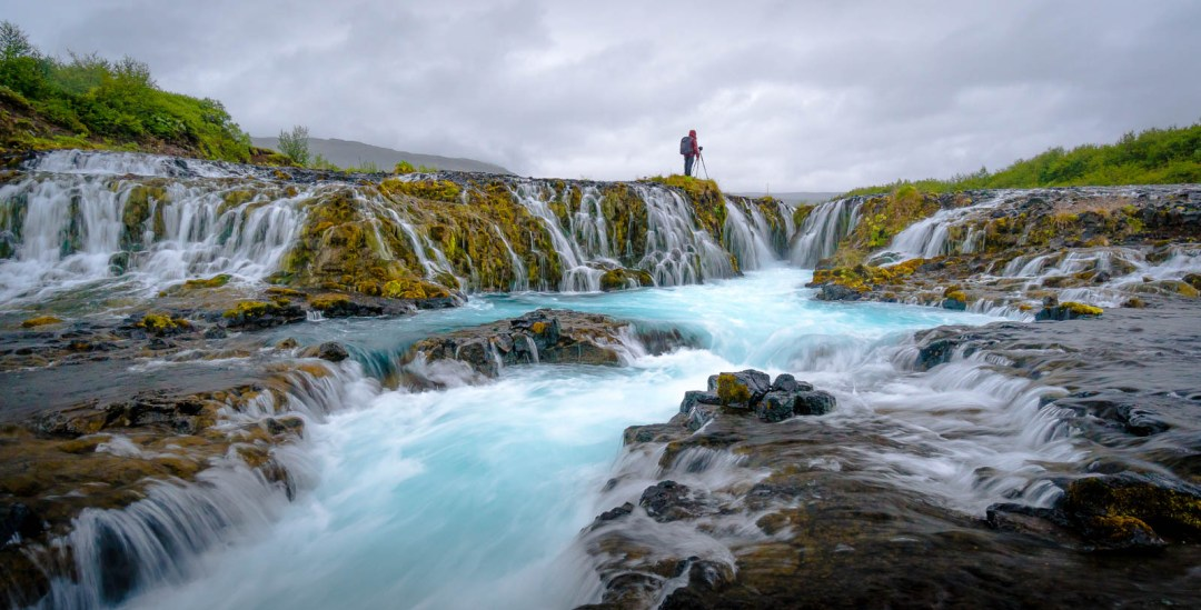 Photographer standing in blue waterfall Bruarfoss Iceland.