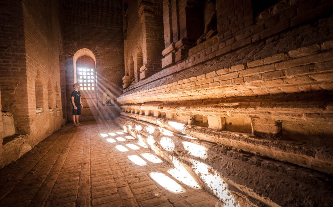 Ben standing inside of dust filled temple in Bagan wtih light coming through window